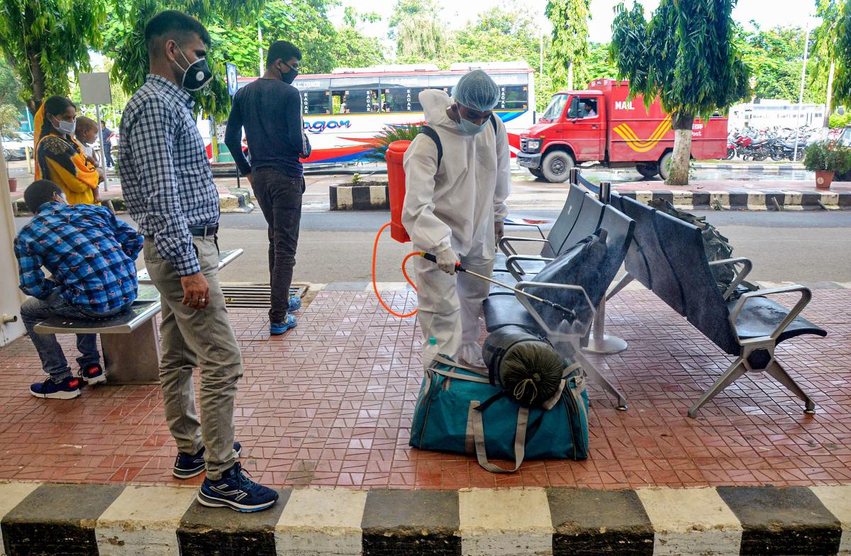 A sanitation worker sprays disinfectant on the luggage of a traveler in Guwahati